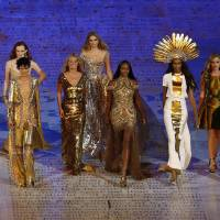 Photo -   FILE - This Sunday Aug. 12, 2012 file photo shows models, from left, Lily Cole, Karen Elson, Stella Tennant, Kate Moss, Lily Donaldson, Naomi Campbell, Jourdan Dunn and Georgia May Jagger walking with a male model during the Closing Ceremony at the 2012 Summer Olympics in London. Models had their moment at the closing ceremony of the London Olympics, with the likes of Kate Moss and Naomi Campbell bringing gold ballgowns, high heels and glamour to the stadium that had been home to sneakers and sweat. The unusual moment seemed to stump even the NBC announcers, who identified Campbell and Moss and otherwise stayed silent for much of the tribute set to David Bowie's