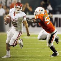 Photo - OU quarterback Landry Jones (12) scrambles away from Miami's Allen Bailey (57) on a fourth down play near the end of the second quarter during the college football game between the University of Oklahoma (OU) Sooners and the University of Miami (UM) Hurricanes at Land Shark Stadium in Miami Gardens, Florida, Saturday, October 3, 2009. Jones threw the ball away on the the play. Photo by Nate Billings, The Oklahoman ORG XMIT: KOD