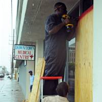 Photo -   Garth Malcolm, left, covers with plywood a primary health center as rain brought by the outer bands of Tropical Storm Sandy falls in Kingston, Jamaica, Tuesday, Oct. 23, 2012. The U.S. National Hurricane Center in Miami said Sandy was expected to become a hurricane as it nears Jamaica on Wednesday. (AP Photo/Collin Reid)