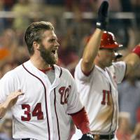 Photo - Washington Nationals Bryce Harper, left, and Ryan Zimmerman cheer on teammate Ian Desmond after scoring on his three-run double during the sixth inning of a baseball game against the Colorado Rockies at Nationals Park, on Monday, June 30, 2014, in Washington. (AP Photo/Evan Vucci)