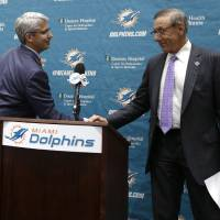 Photo - Dennis Hickey, left, the new general manager for the Miami Dolphins NFL football team, shakes hands with team owner Stephen Ross during a news conference Tuesday, Jan. 28, 2014, in Davie, Fla. (AP Photo/Lynne Sladky)