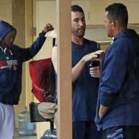 Photo - Detroit Tigers' Justin Verlander, center, talks with Miguel Cabrera, right, as Tigers players gather outside their locker room while waiting for an exhibition spring training baseball game between the Detroit Tigers and the Philadelphia Phillies to be called due to rain in Lakeland, Fla., Thursday, March 6, 2014. (AP Photo/Gene J. Puskar)