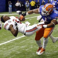 Photo - Florida linebacker Jon Bostic (1) hits Louisville quarterback Teddy Bridgewater (5) hard enough to dislodge his helmet in the first quarter of the Sugar Bowl NCAA college football game Wednesday, Jan. 2, 2013, in New Orleans. (AP Photo/Bill Haber)