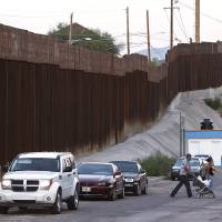 Photo -   In this Aug. 9, 2012, photo, vehicles are parked along the border fence as pedestrians cross the street in Nogales, Mexico. The location is near the site where a U.S. Border Patrol agent being pelted with rocks opened fire toward Mexico, killing a 16-year-old boy. The shooting has prompted renewed outcry over the Border Patrol's use-of-force policies and angered human rights activists and Mexican officials who believe the incident has become part of a disturbing trend along the border _ gunning down rock-throwers rather than using non-lethal weapons. (AP Photo/Ross D. Franklin)