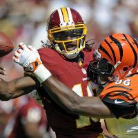 Photo -   Cincinnati Bengals defensive end Carlos Dunlap sacks Washington Redskins quarterback Robert Griffin III and forces a fumble during the first half of an NFL football game in Landover, Md., Sunday, Sept. 23, 2012. (AP Photo/Nick Wass)