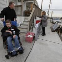Photo - Chris Troy and his wheelchair-bound son Connor, 12, who suffers from a life-threatening neuromuscular disease, waits for wife Kerry Ann to get the mail in Long Beach, N.Y., Wednesday, Dec. 12, 2012, after visiting their home, which is under renovation after it was seriously damaged by Superstorm Sandy. Due to the kindness of strangers, the Troy's are staying in a nearby house in Point  Lookout, N.Y. All the renovations to the home are being paid for by businessman Donald Denihan, who has ordered his workers to have the Long Beach house ready by Christmas. (AP Photo/Kathy Willens)