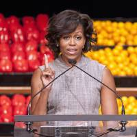 Photo - FILE - In this Jan. 20, 2011 file photo, first lady Michelle Obama takes part in Wal-Mart's announcement of a comprehensive effort to provide healthier and more affordable food choices to their customers, in Washington. Recent changes put in place by the food industry are in response to the campaign against childhood obesity that Obama began waging three years ago. (AP Photo/Cliff Owen, File)