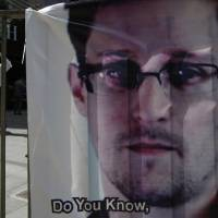 Photo - A banner supporting Edward Snowden, a former CIA employee who leaked top-secret documents about sweeping U.S. surveillance programs, is displayed at Central, Hong Kong's business district, Friday, June 21, 2013. U.S. President Barack Obama is holding his first meeting with a privacy and civil liberties board Friday as he seeks to make good on his pledge to have a public discussion about secretive government surveillance programs. (AP Photo/Kin Cheung)