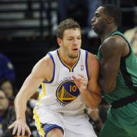 Photo - Golden State Warriors' David Lee drives toward the basket as Boston Celtics' Brandon Bass defends during the first half of an NBA basketball game in Oakland, Calif., Saturday, Dec. 29, 2012. (AP Photo/George Nikitin)