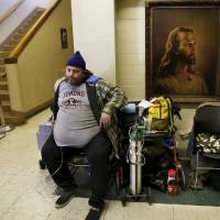 Photo - Jon Peterson, who must use oxygen because he has COPD (chronic obstructive pulmonary disease),  sits in a hallway inside the Jesus House. Peterson was among the many homeless people in Oklahoma City dealing with frigid sub-freezing temperatures, part of a major winter storm that continues to grip much of the central sections and the eastern half of the United States. Photo taken Monday, Jan. 6, 2014.  Photo by Jim Beckel, The Oklahoman