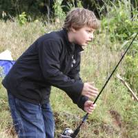 Photo - Devyn Fisher, 7, tries his luck at the Kids Fishing Derby at Arcadia Lake. PHOTOS BY PAUL HELLSTERN, THE OKLAHOMAN
