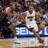 Photo - FILE - In this Nov. 10, 2008, file photo, Miami Heat guard Daequan Cook (14) cuts around New Jersey Nets forward Bobby Simmons (21) during the fourth quarter of an NBA basketball game in Miami. The Heat traded Cook and the No. 18 pick in the draft to the Oklahoma City Thunder.  The deal announced by the Heat on Wednesday, june 23, 2010, clears about $3.4 million in salary cap space as Miami gets ready for next week's start of free agency.  Miami acquired the No. 32 selection from Oklahoma City to complete the deal.  (AP Photo/Steve Mitchell) ORG XMIT: NY160