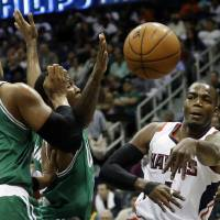 Photo - Atlanta Hawks' Paul Millsap, right, passes the ball past Boston Celtics' Jared Sullinger, left, and Chris Johnson in the second quarter of an NBA basketball game, Wednesday, April 9, 2014, in Atlanta. (AP Photo/David Goldman)