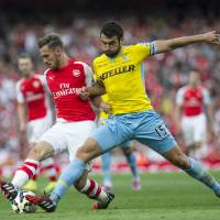 Photo - Arsenal's Aaron Ramsey, left, fights for the ball with Crystal Palace's Mile Jedinak during their English Premier League soccer match at Emirates Stadium, in London, Saturday, Aug. 16, 2014. (AP Photo/Bogdan Maran)
