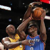 Photo - Oklahoma City Thunder Serge Ibaka of Congo has his shot smothered by Los Angeles Lakers forward Lamar Odom in the second half during game 2 of a first-round NBA basketball playoff series, Tuesday, April 20, 2010, in Los Angeles. Lakers won 95-92.(AP Photo/Alex Gallardo) ORG XMIT: LAS107