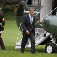 Photo - President Barack Obama walks from the Marine One helicopter on the South Lawn of the White House in Washington, Tuesday, Nov. 5, 2013, to the  Oval Office after a trip to Walter Reed National Military Medical Center to visit with wounded troops. (AP Photo/ Evan Vucci)