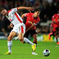 Photo - MK Dons' Antony Kay, left, tussles with Manchester United's Javier Hernandez during the League Cup Second Round match at Stadium:mk, Milton Keynes, England, Tuesday Aug. 26, 2014. MK Dons defeated Manchester United 4-0. (AP Photo/PA, Nick Potts) UNITED KINGDOM OUT  NO SALES  NO ARCHIVE