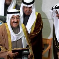 Photo - The Amir of Kuwait, Sheikh Sabah Al Sabah, left, receives a copy of a speech given by Kuwait's Prime Minister, Sheikh Jaber al-Mubarak al-Sabah, second right, during the inauguration of the 14th Legislative Term of the National Assembly in Kuwait, Sunda,  Dec 16, 2012. Security forces blocked hundreds of protesters from staging a rally outside the parliament building Sunday, as Kuwait's amir denounced anti-government factions as committing