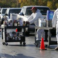 Photo - Workers unload paint cans from vehicles Saturday during the city's Household Hazardous Waste Event at the Lloyd Noble Center in Norman. PHOTO BY STEVE SISNEY, THE OKLAHOMAN  STEVE SISNEY