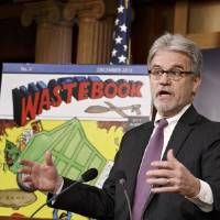 "Photo - FILE - In this Dec. 17, 2013 file photo, Sen. Tom Coburn, R-Okla., a longtime deficit hawk, outlines his annual ""Wastebook,"" which points a critical finger at billions of dollars in questionable government spending during a news conference on Capitol Hill in Washington. (AP Photo/J. Scott Applewhite, File)"
