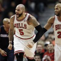 Photo - Chicago Bulls forward Carlos Boozer (5), reacts after scoring against the Charlotte Bobcats next to Chicago Bulls forward Taj Gibson (22) during the first half of an NBA basketball game in Chicago, Saturday, Jan. 11, 2014. (AP Photo/Kamil Krzaczynski)