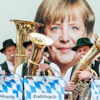 Photo - Members of a traditional Bavarian band play in front of an election Poster of German Chancellor Angela Merkel in Miesbach, southern Germany, Wednesday, Sept. 11, 2013. Germany faces general elections on Sept. 22, 2013. (AP Photo/dpa, Marc Mueller)