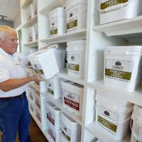 Photo - Employee Chuck Travis puts a container of emergency food on the shelf at the Homeland Preparation Station  store, which opened this week.  Steve Gooch - The Oklahoman