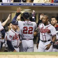 Photo - Atlanta Braves' Jason Heyward celebrates with teammates after scoring the tying run in the eighth inning on a single by Chris Johnson against the San Diego Padres of a baseball game Saturday, Aug. 2, 2014, in San Diego. (AP Photo/Don Boomer)
