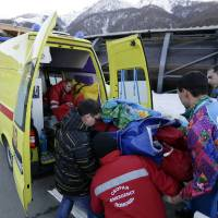 Photo - A track worker is loaded into an ambulance after he was injured when a forerunner bobsled hit him just before the start of the men's two-man bobsled training at the 2014 Winter Olympics, Thursday, Feb. 13, 2014, in Krasnaya Polyana, Russia. (AP Photo/Charlie Riedel)