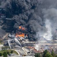 Photo - Smoke rises from railway cars that were carrying crude oil after derailing in downtown Lac Megantic, Quebec, Canada, Saturday, July 6, 2013. A large swath of Lac Megantic was destroyed Saturday after a train carrying crude oil derailed, sparking several explosions and forcing the evacuation of up to 1,000 people. (AP Photo/The Canadian Press, Paul Chiasson)