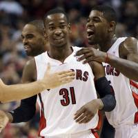 Photo - Toronto Raptors guard Terrence Ross (31) is congratulated by Amir Johnson, right, and Alan Anderson, left, after making a buzzer-beating 3-pointer against the Portland Trail Blazers at the end of the first half of an NBA basketball game in Toronto, Wednesday, Jan. 2, 2013. (AP Photo/The Canadian Press, Frank Gunn) ORG XMIT: FNG103