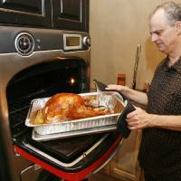 Photo - LINDY RAPPAPORT / LORI RAPPAPORT: Claude Rappaport removes a turkey from his TurboChef Oven after cooking for 39 minutes at his store, Culinary Kitchens, in Oklahoma City, OK, Saturday, Nov. 14, 2009. Claude, Lindy and Lori Rappaport with help from their friend Clayton Bahr will be cooking turkeys for the homeless on Nov. 24, using the latest technology to cook up to 100 turkeys the day before Thanksgiving. By Paul Hellstern, The Oklahoman ORG XMIT: KOD