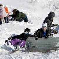 Photo - Sledders slide down the embankment on Interstate 35 at Tecumseh Rd. on Christmas Day on Friday, Dec. 25, 2009, in Norman, Okla. after a record snowstorm. Photo by Steve Sisney