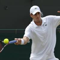 Photo - John Isner of U.S. plays a return to Feliciano Lopez of Spain during their men's singles match at the All England Lawn Tennis Championships in Wimbledon, London, Monday, June 30, 2014. (AP Photo/Pavel Golovkin)
