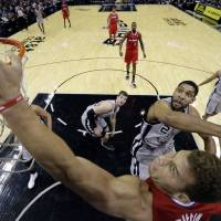 Photo - Los Angeles Clippers' Blake Griffin, foreground, scores as San Antonio Spurs' Tim Duncan (21) tries to defend him during the first half on an NBA basketball game, Saturday, Jan. 4, 2014, in San Antonio. (AP Photo/Eric Gay)