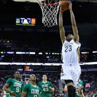 Photo - New Orleans Pelicans forward Anthony Davis (23) shoots past Boston Celtics guard Rajon Rondo (9), guard Avery Bradley (0), center Kris Humphries (43) and center Kelly Olynyk, right, during the first half of an NBA basketball game in New Orleans, Sunday, March 16, 2014. (AP Photo/Jonathan Bachman)