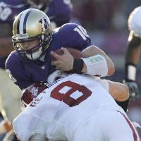Photo - Oklahoma's Ryan Reynolds (8) stops Washington quarterback Jake Locker (10) in the first half during the college football game between the University of Oklahoma (OU) and Washington at Husky Stadium in Seattle, Wash., Saturday, September 13, 2008. BY NATE BILLINGS, THE OKLAHOMAN ORG XMIT: KOD