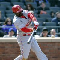 Photo - Cincinnati Reds second baseman Brandon Phillips hits a two-run home run in the seventh inning of a baseball game against the New York Mets at Citi Field, Saturday, April 5, 2014, in New York. (AP Photo/John Minchillo)