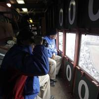 Photo - In this April 10, 2014 photo, scoreboard operators Brian Helmus, left, and Fred Washington look out to the field from inside the iconic scoreboard at Wrigley Field during a baseball game between Pittsburgh Pirates and Chicago Cubs, in Chicago. With Boston's Fenway Park and Wrigley the only two stadiums in the majors with primary manual scoreboards, it has been a job largely shrouded in mystery until the Cubs allowed The Associated Press climb the steel ladder through the steel floor of the scoreboard for a rare visit to mark Wrigley's 100-year anniversary. (AP Photo/Kiichiro Sato)