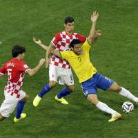 Photo - Brazil's Fred, right, falls after making contact with Croatia's Dejan Lovren during the group A World Cup soccer match between Brazil and Croatia, the opening game of the tournament, in the Itaquerao Stadium in Sao Paulo, Brazil, Thursday, June 12, 2014. At left is Croatia's Vedran Corluka. (AP Photo/Thanassis Stavrakis)