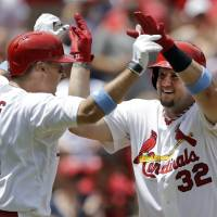 Photo - St. Louis Cardinals' Matt Adams, right, is congratulated by teammate Allen Craig after hitting a two-run home run during the second inning of a baseball game against the Washington Nationals, Sunday, June 15, 2014, in St. Louis. (AP Photo/Jeff Roberson)