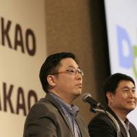 Photo - Daum Communications Corp. CEO Choi Sae-hoon, left, and Kakao Corp. CEO Sirgoo Lee listen to reporter's question during a press conference in Seoul, South Korea, Monday, May 26, 2014. Mobile messenger service Kakao Talk is seeking a backdoor listing on the South Korean stock exchange by combining with the country's second largest Internet portal. Daum Communications Corp. and Kakao Corp. said Monday that Kakao shareholders will get 1.556 Daum shares for each Kakao share they own. (AP Photo/Lee Jin-man)
