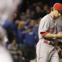 Photo -   Cincinnati Reds starter Mike Leake checks the ball after Chicago Cubs' Alfonso Soriano hit a two-run home run during the sixth inning of a baseball game in Chicago, Wednesday, Sept. 19, 2012. (AP Photo/Nam Y. Huh)