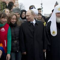 Photo -   Russian President Vladimir Putin, front centre, speaks with guests and religious leaders of various faiths after a ceremony at the statue of Minin and Pozharsky, the leaders of a struggle against foreign invaders in 1612, to mark the National Unity Day, at the Red Square in Moscow, Sunday, Nov. 4, 2012. The new holiday was created in 2005 to replace the traditional Nov. 7 celebration of the 1917 Bolshevik rise to power. The Kremlin has tried to give it historical significance by tying it to the 1612 expulsion of Polish and Cossack troops who briefly seized Moscow at a time of political disarray. But it has been seized upon by extreme nationalists. (AP Photo/ Misha Japaridze)