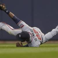 Photo - Atlanta Braves' Jason Heyward makes a sliding catch on a ball hit by Milwaukee Brewers' Carlos Gomes during the ninth inning of a baseball game Wednesday, April 2, 2014, in Milwaukee. Atlanta won 1-0. (AP Photo/Jeffrey Phelps)