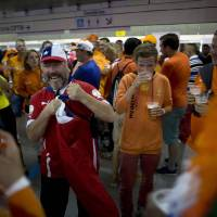 Photo - A Chile soccer fans jokes around with Dutch soccer fans at a subway station on their way to the World Cup group B match between Chile and the Netherlands at the Itaquerao stadium in Sao Paulo, Brazil, Monday, June 23, 2014. Both teams having already qualified for the round of 16, Monday's match will decide which of them wins Group B. (AP Photo/Dario Lopez-Mills)