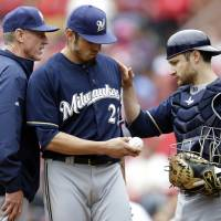 Photo - Milwaukee Brewers starting pitcher Matt Garza, center, gets a pat on the back from catcher Jonathan Lucroy while leaving a baseball game due to an injury as manager Ron Roenicke, left, stands by during the fourth inning of a baseball game against the St. Louis Cardinals Wednesday, April 30, 2014, in St. Louis. (AP Photo/Jeff Roberson)