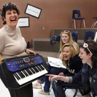 Photo - Bonnie Sneed, director of choirs at Choctaw High School, shows an electronic keyboard to members of one of her choral groups. She is seeking donations of keyboards from community residents for use by choir members. Photos by Jim Beckel, The Oklahoman