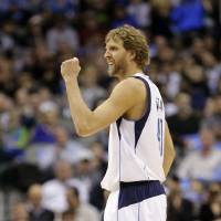 Photo - Dallas Mavericks' Dirk Nowitzki, of Germany, celebrates after sinking a long basket and getting a foul call in his favor early in the first half of an NBA basketball game against the Orlando Magic on Wednesday, Feb. 20, 2013, in Dallas. (AP Photo/Tony Gutierrez)