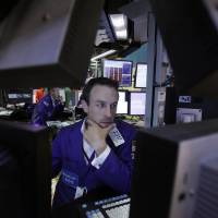 Photo -   FILE - In this June 1, 2012 file photo, Specialist Christopher Trotta is framed by screens as he works at his post on the floor of the New York Stock Exchange. U.S. stock futures are rebounding Monday, June 4, 2012, from a 275-point plunge Friday even with markets in Europe and Asia slumping. (AP Photo/Richard Drew, File)